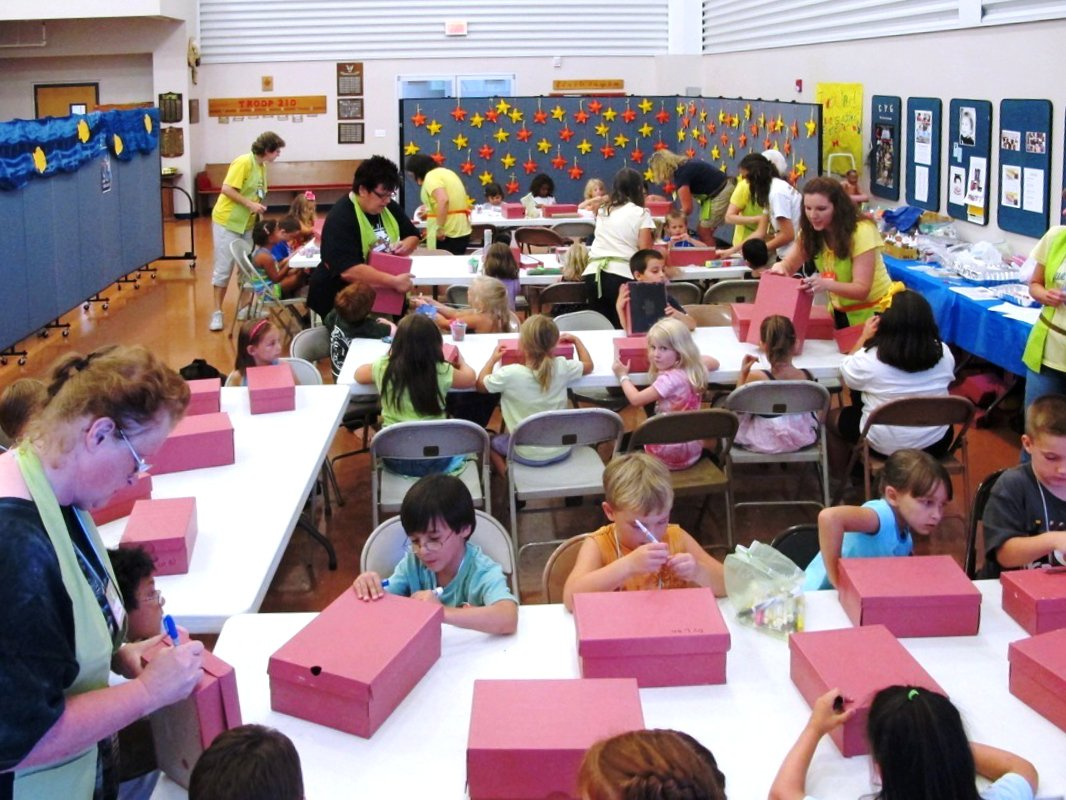 Adult staff assist students at a Vacation Bible School draw on red shoe boxes while sitting at long tables.