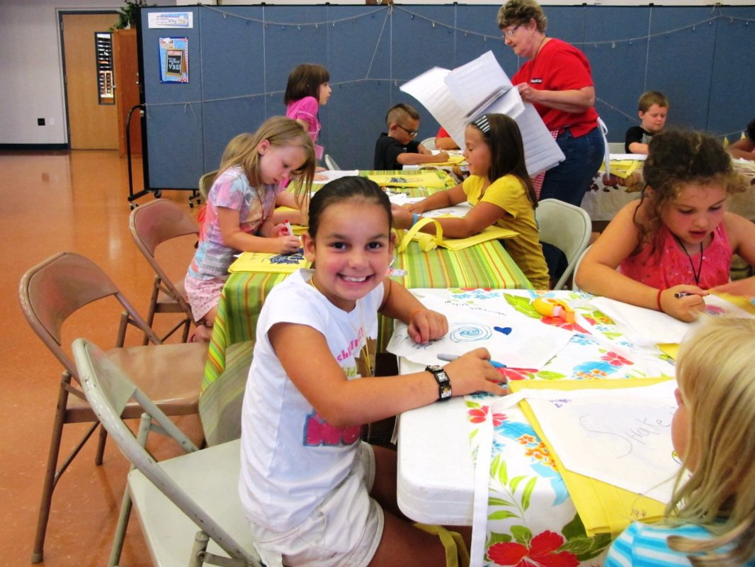 An elementary student stops coloring to pose for a picture during craft time at VBS.