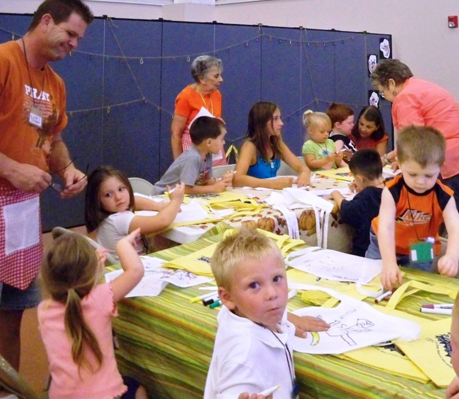 Male and Female adults helps young students color pictures during craft time at a VBS camp.