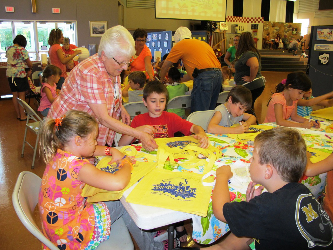 Adult staff assist young VBS students decorate their activitiy bag to be used throughout the week.