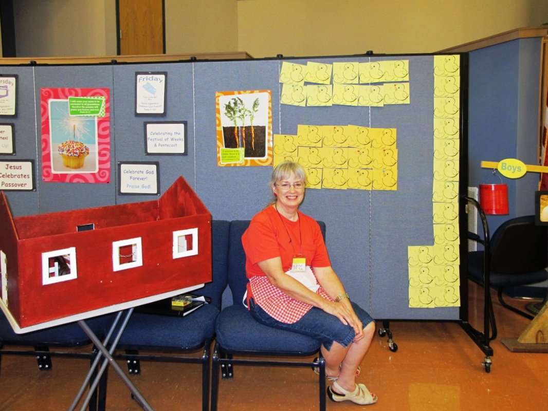 A lady sits on a chair next to a game board created on a portable room divider.