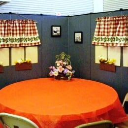 A round table covered in an orange table cloth sits at the center of room dividers decorated to resemble a restaurant.