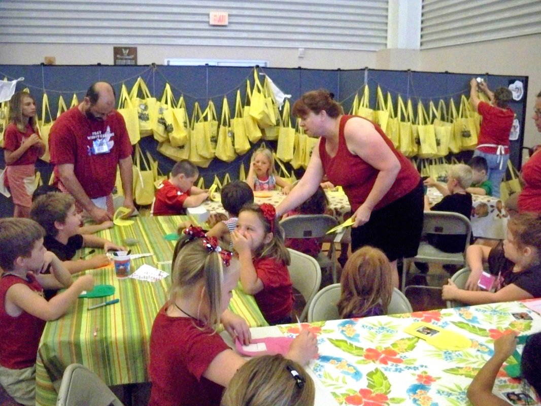 Yellow book bags hang on the sides of Screenflex Room Dividers while adults help students complete VBS crafts.
