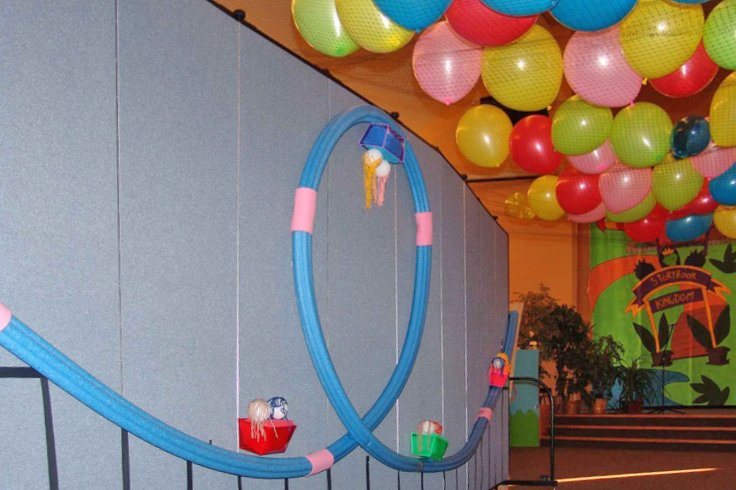 A roller coaster made from pool tubes is tacked to a Screenflex Room Dividers. Balloons rest on nets hanging from the ceiling.