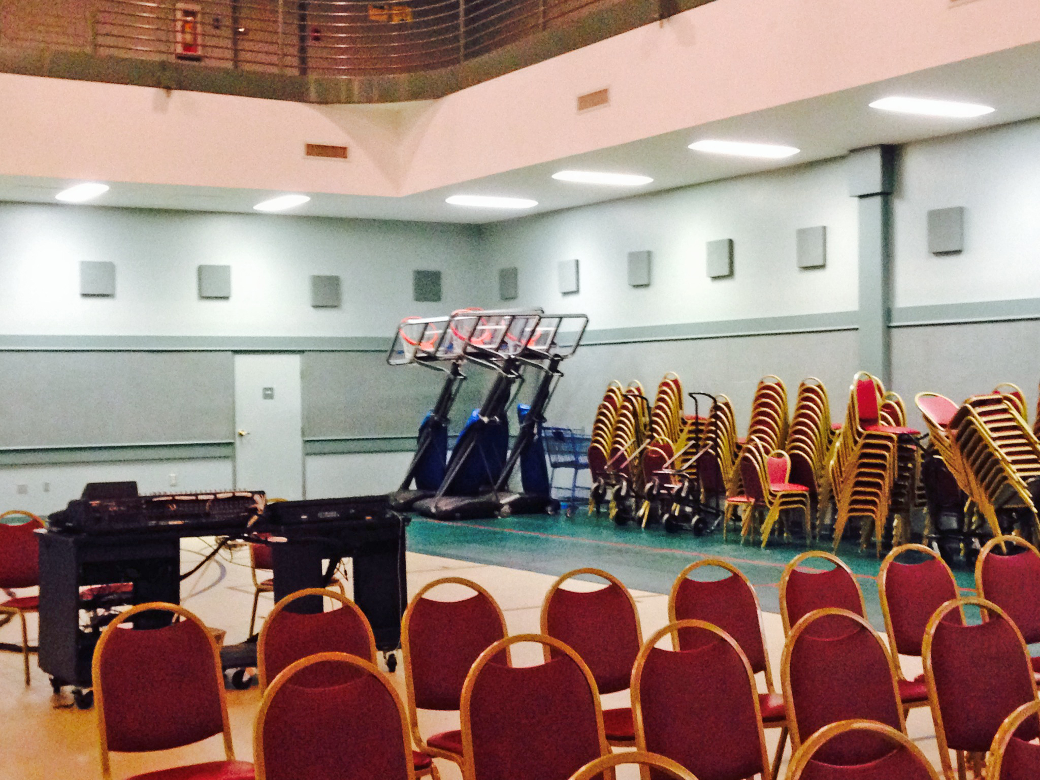 Rows of chair are set up to create a church sanctuary inside a gym. Additional chairs and basketball hoops are set out of the way against the wall.