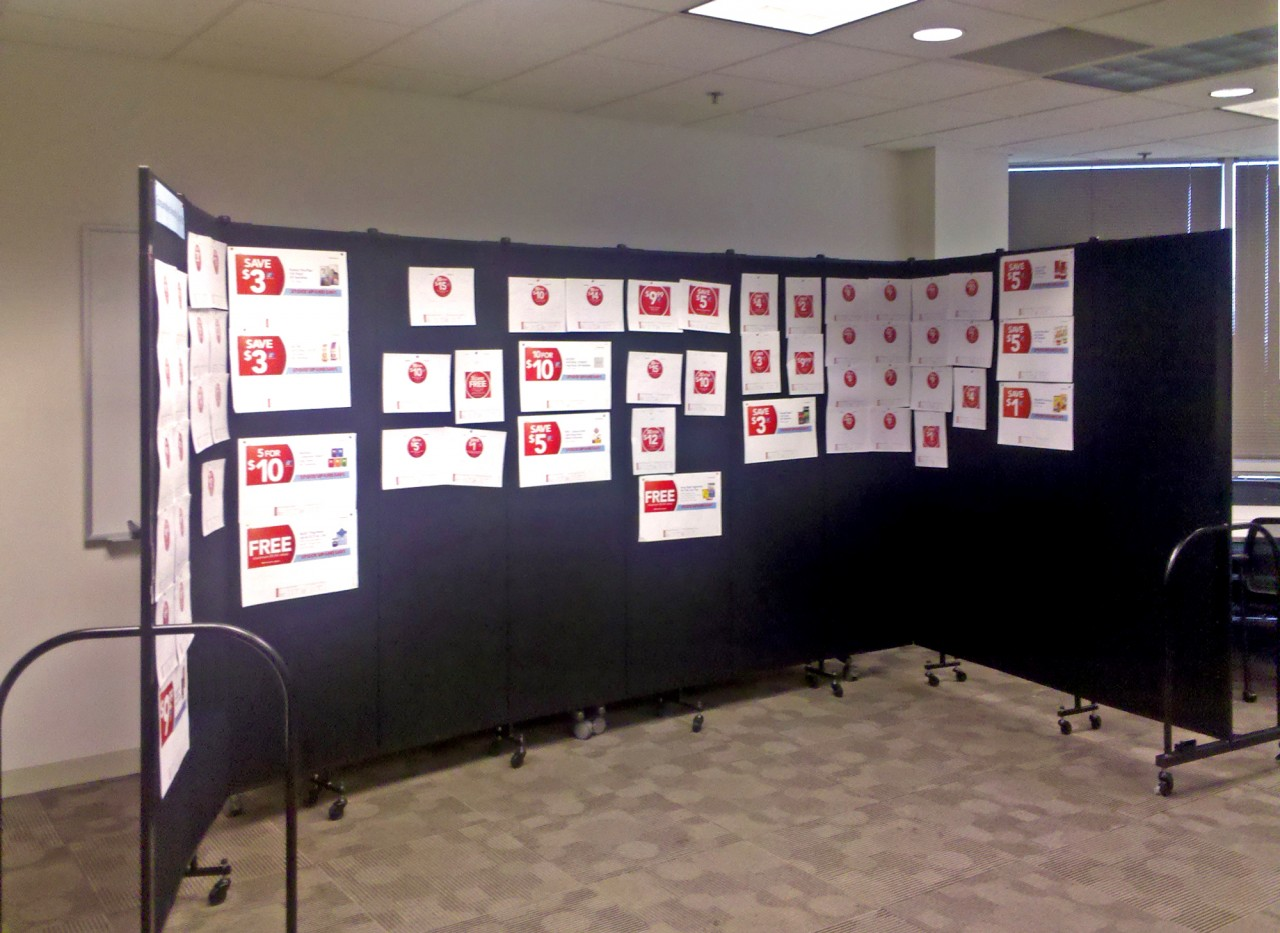 Storyboard presentation displayd on black Screenflex Room Dividers in an office hallway.