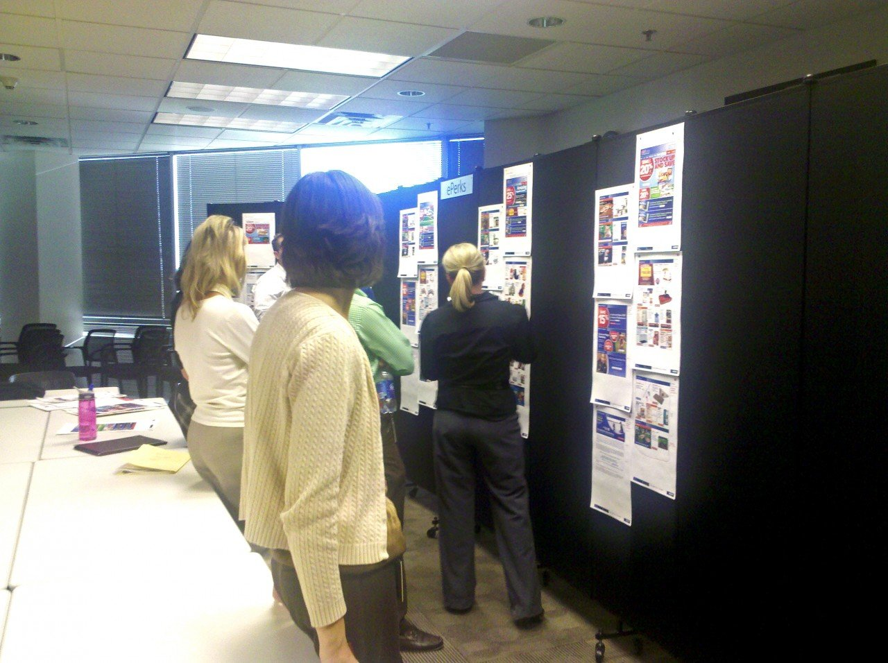 A small group of employees review several storyboard layouts tacked to a black Screenflex Room Divider.