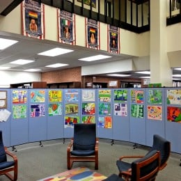 Student artwork tacked to rolling walls and displayed in a school library
