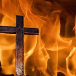 Vibrant orange flames surround a brown rusted cross.