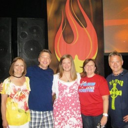 A group of adult male and female youth ministry leaders in front of a painted flame and speakers.