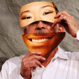 A caucasian man holding an image of an Asian female's eyes over his own and the mouth of an African American covers his own mouth.