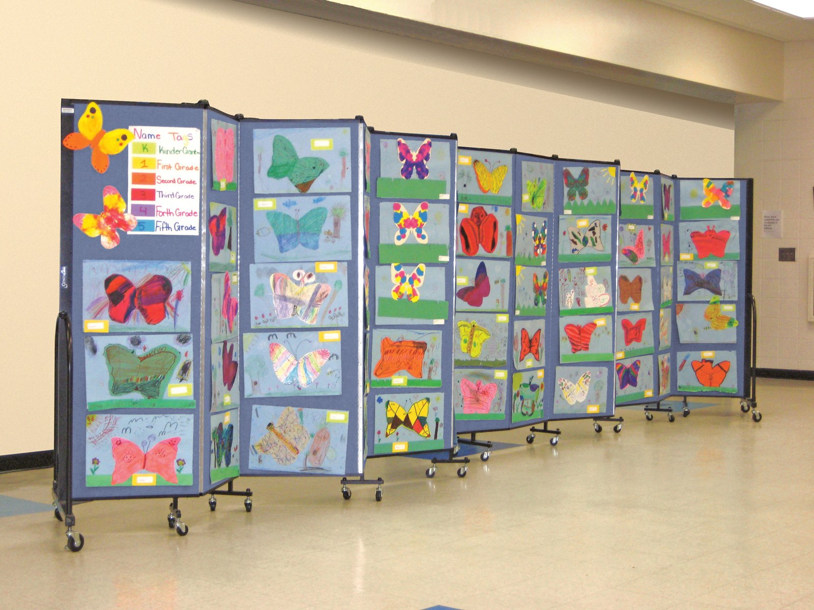 Artwork displayed on a blue portable room dividers in a school hallway.