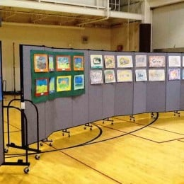 Student artwork displayed on two 11 panel Screenflex room dividers in a gymnasium