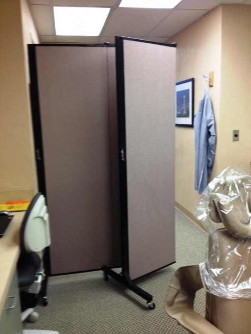A portable divider wall creating a private dental operatory room