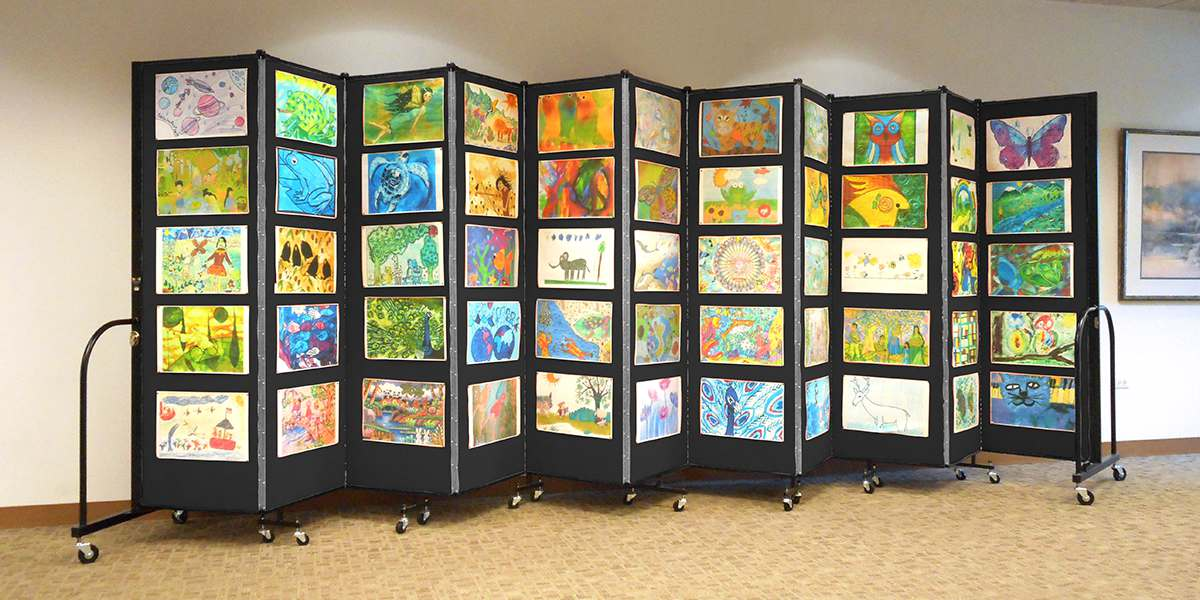 A black accordion room divider decorated with colorful children artwork