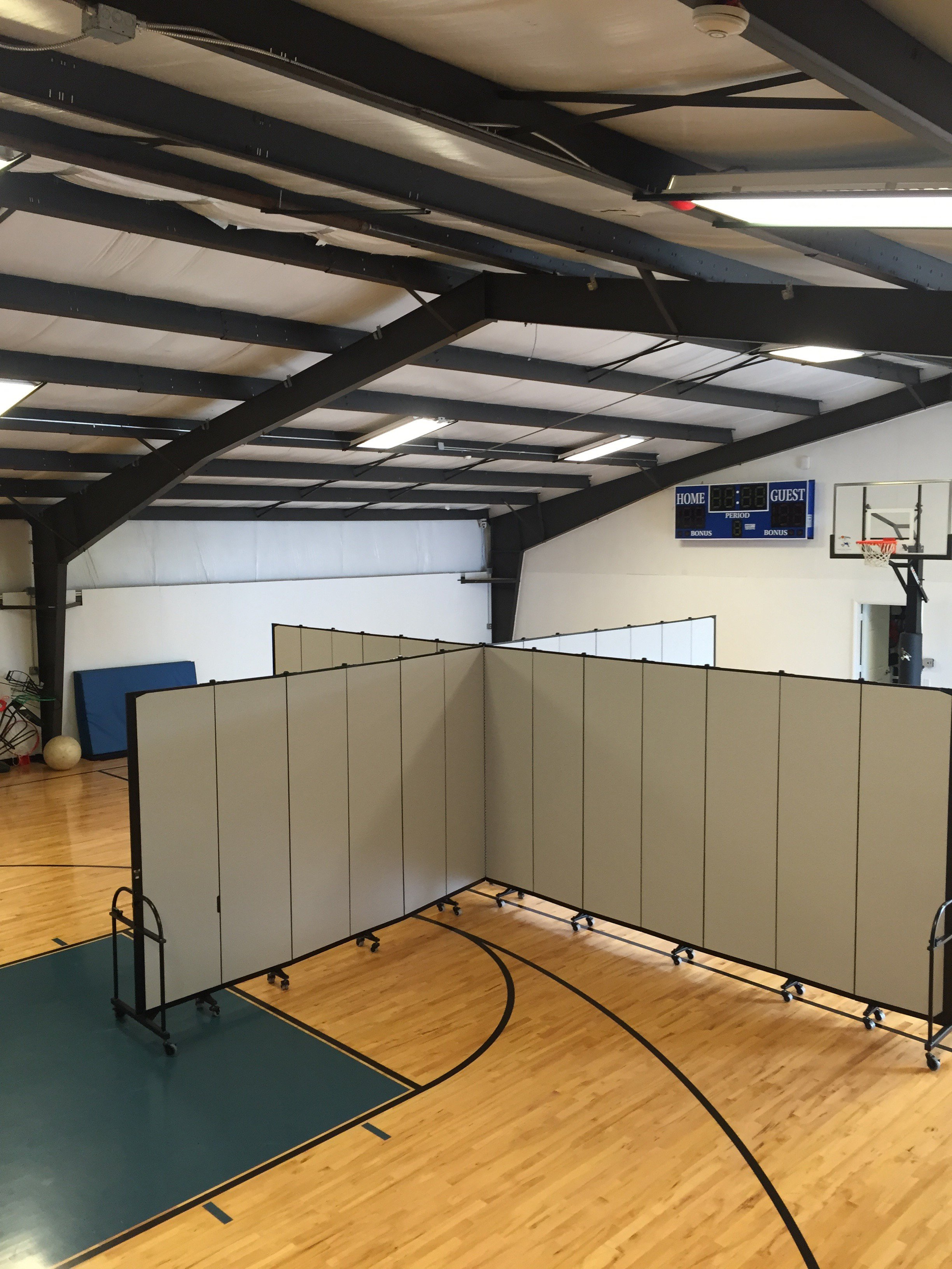 Two room dividers are connected to create 4 rooms in a gym