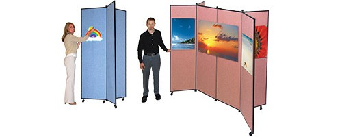 A woman tacks an image onto a 3-panel display tower and a man stands next to a 6-panel display tower