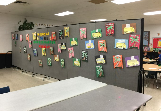 Student artwork is hung a portable wall that creates a classroom in the corner of a large room