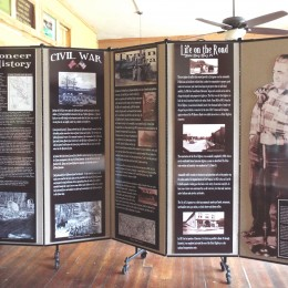 Historical museum display information hung on a 5 panel room divider