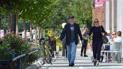 A couple walks hand in hand down a small town city sidewalk