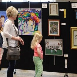 A women and two girls view a collection of artwork hung on a black portable wall