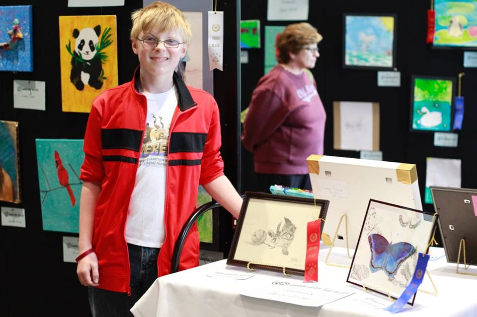 An teen art show contestant poses with his artwork on a table