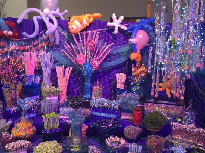 Tables cloths are draped over a potable wall to create the perfect backdrop to a sea themed candy table