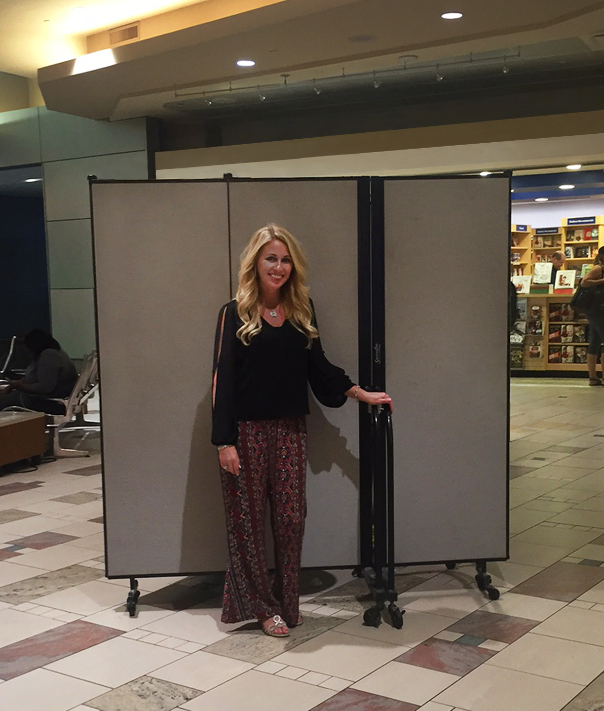 A woman stands in front of a portable wall on wheels in an airport