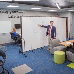 Staff use a moveable office partition to divide meeting space