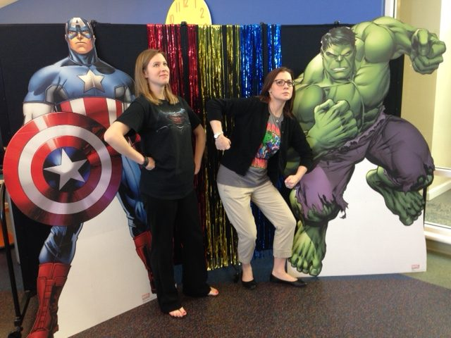 Life-size posters of superheroes flank the sides two librarians posing in front of a black room divider