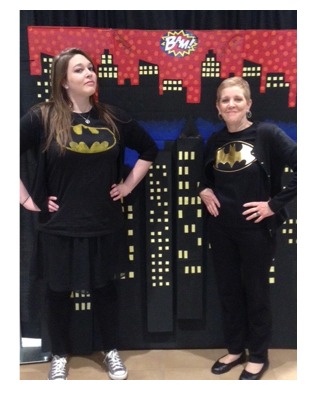 A pair of female librarians with batman t-shirts pose in front of a painted cartoon skyline