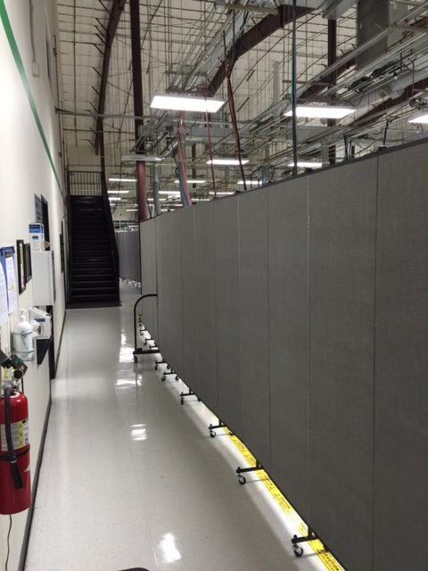 A long line of portable room dividers separate a portion of a factory from other employees