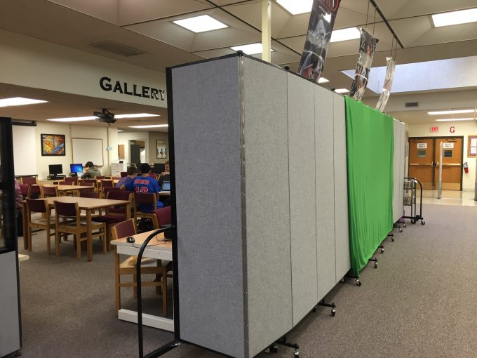 A green screen is hung from a portable wall in a library