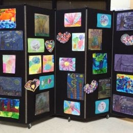 Children's artwork displayed on a black portable wall