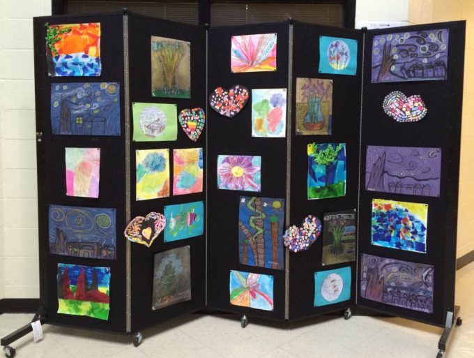 Children's artwork displayed on a black portable display wall