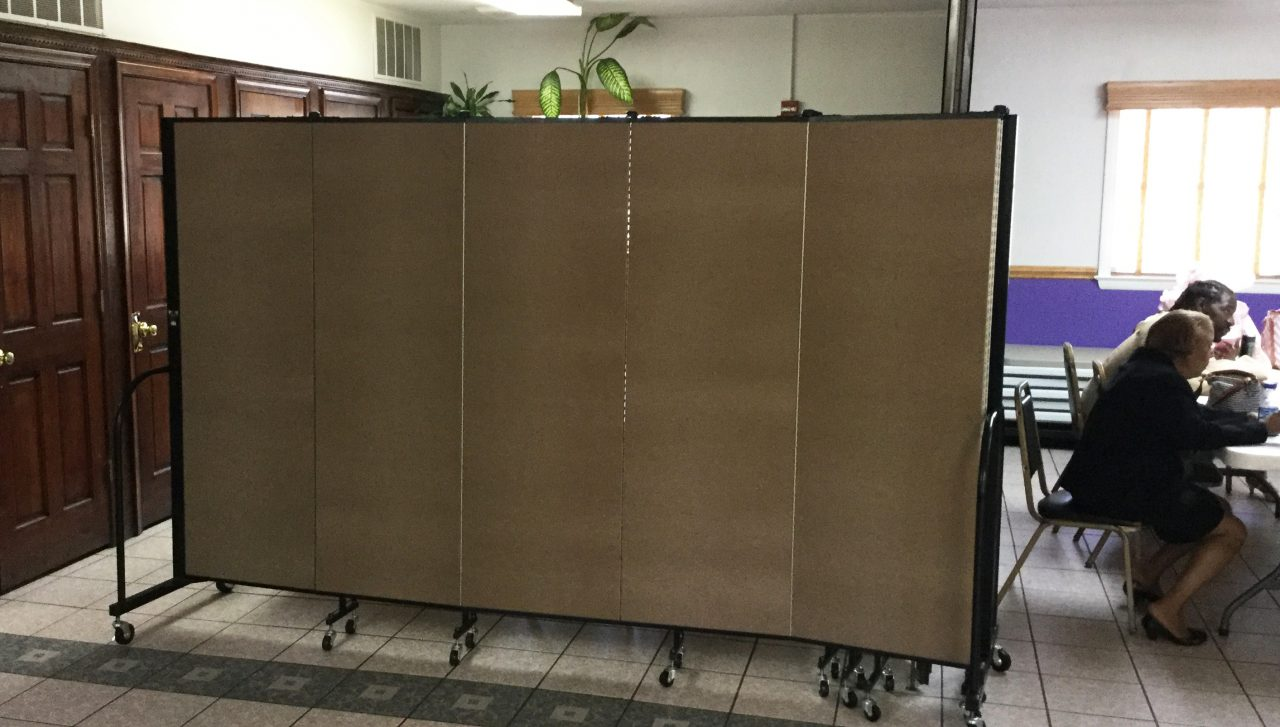 A folding room divider creates a storage area in a fellowship hall