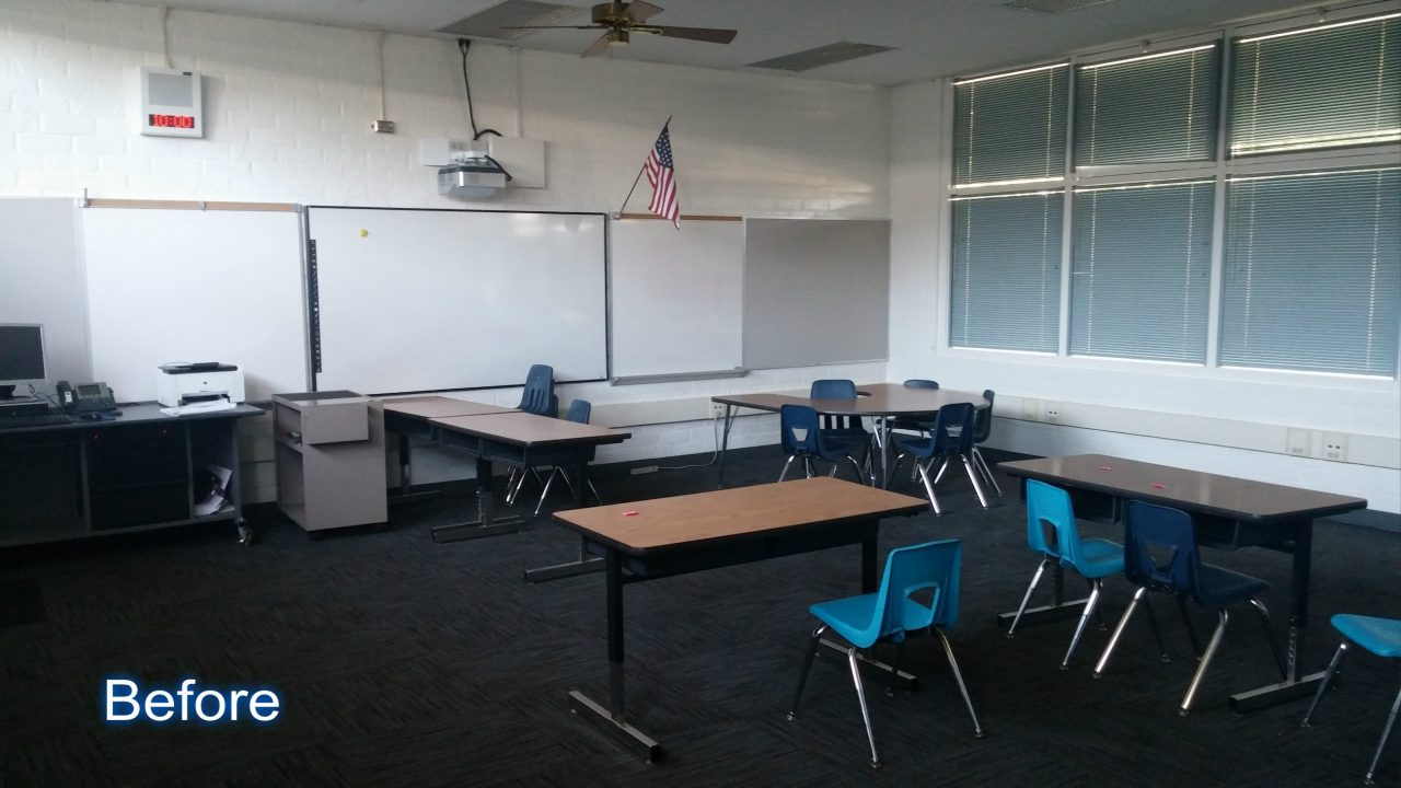 An open classroom with tables and chairs for the teacher and students