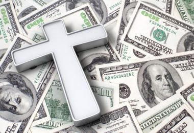 A cross laying on top of 100 dollar bills