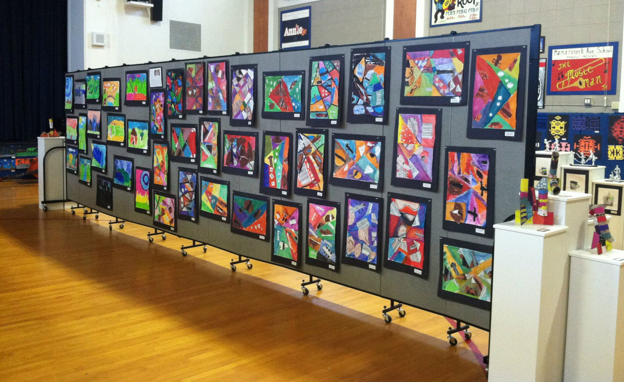 Tackable walls are used to display student artwork in a gymnasium with a wood floor