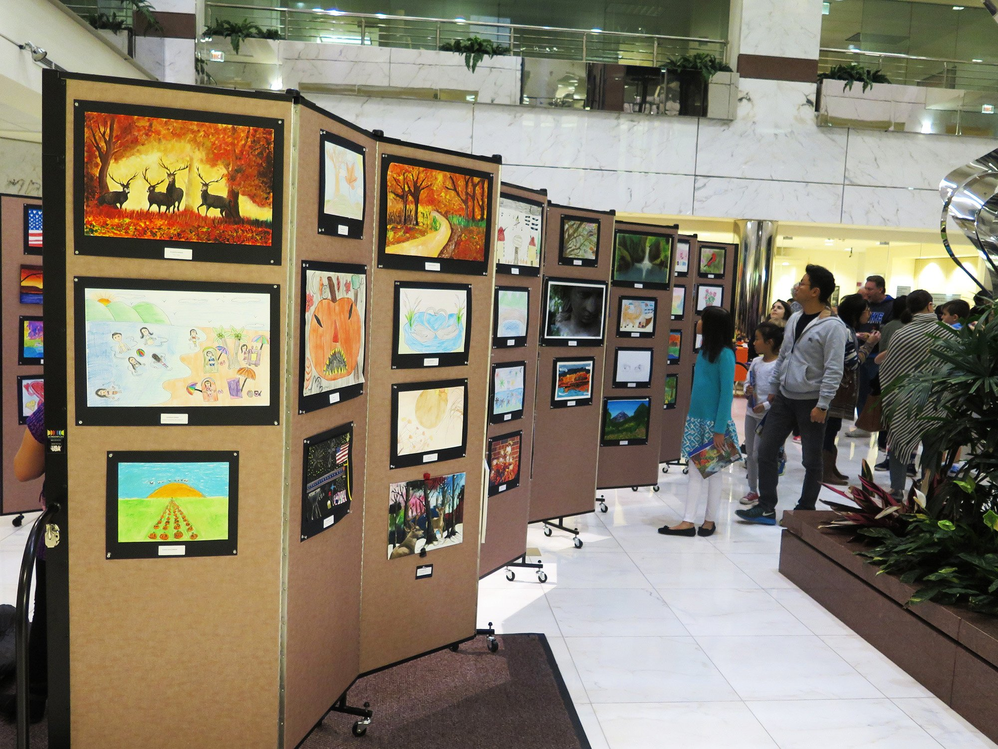 Movable art show display system allows a bank to showcase student artwork