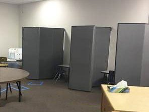 Three classroom partitions separate three desks from each other