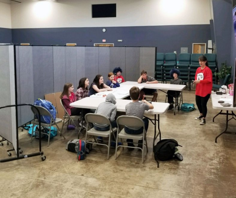 A teacher talks to a group of students sitting at a table