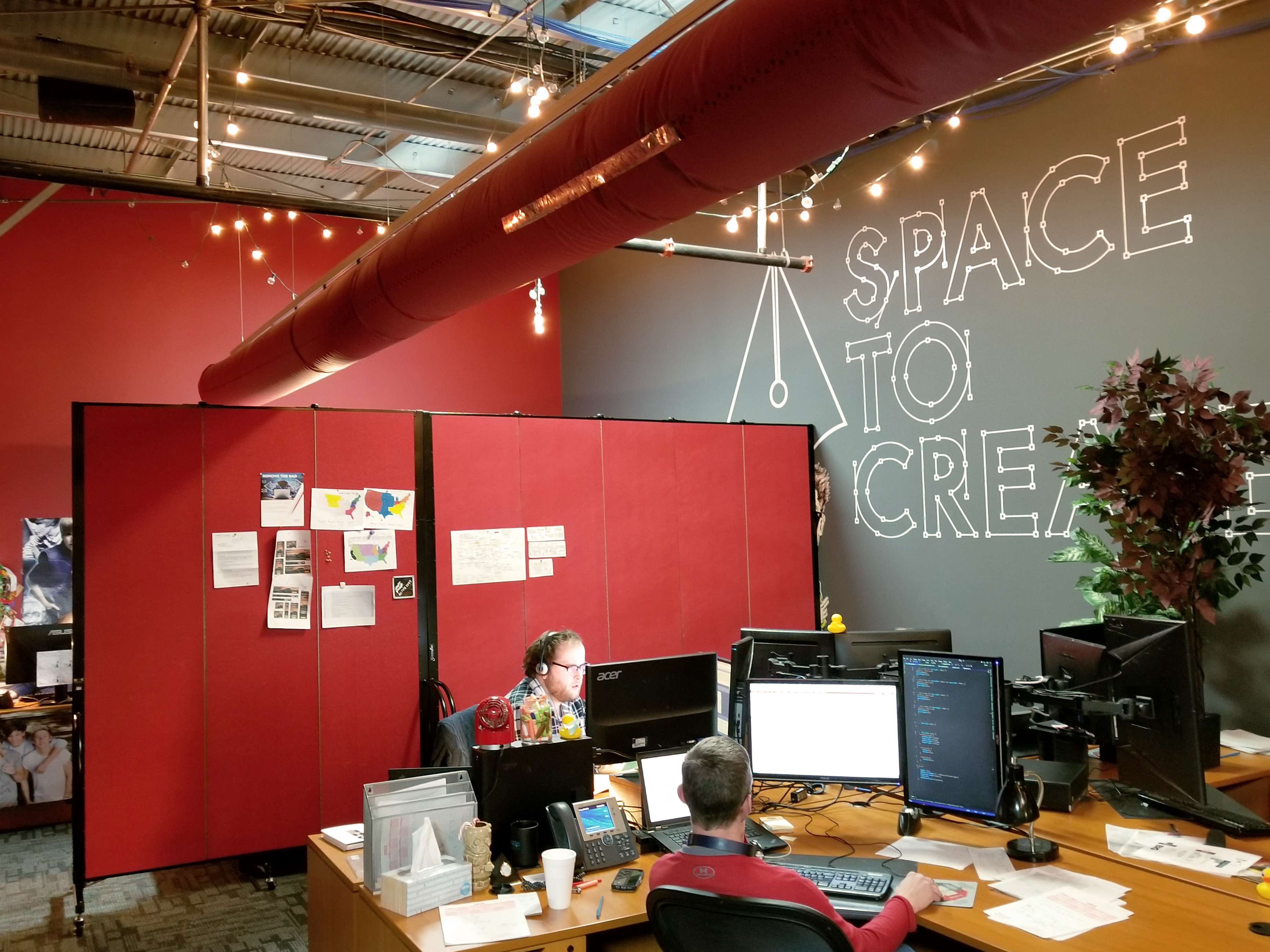 A set of red tackable room dividers separate an office into two rooms