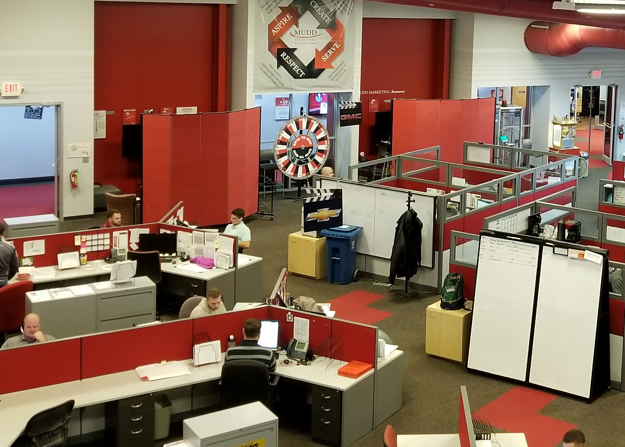A set of red dividers provide private meeting space in a crowded open office space