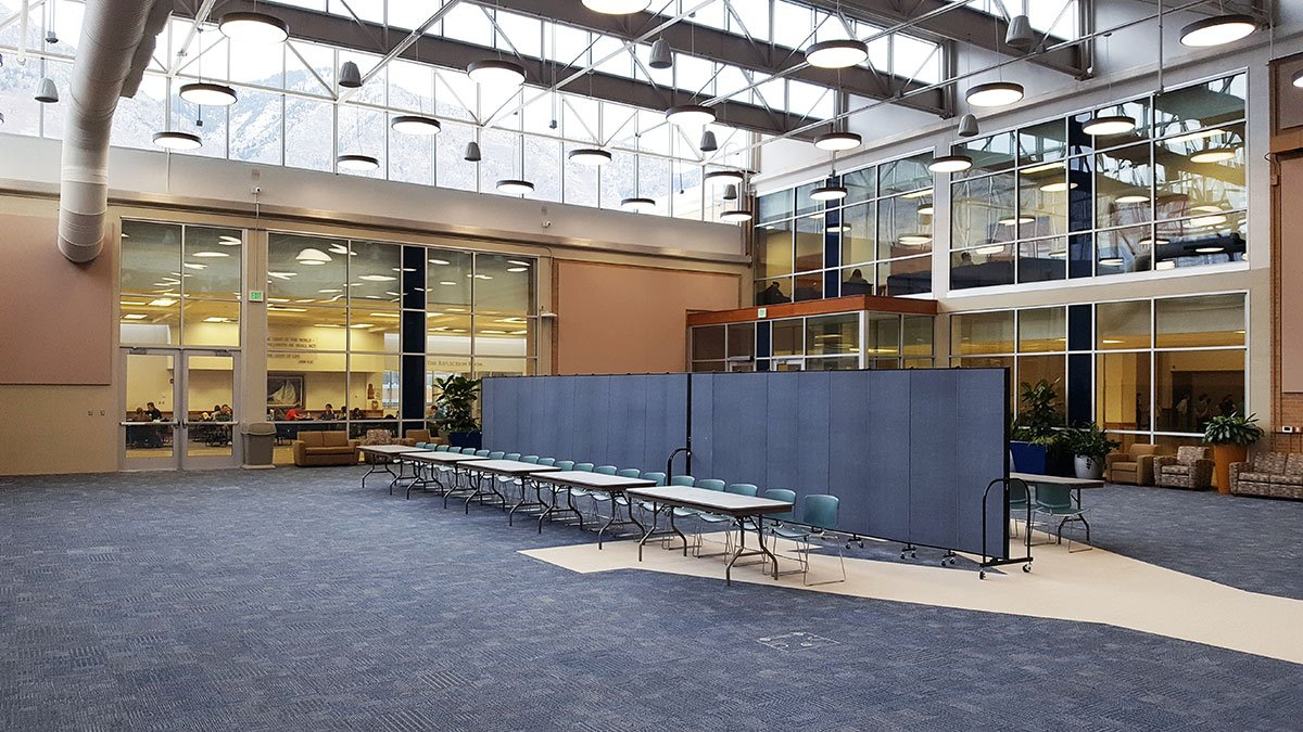 A set up two blue room dividers adjoined to create a division in a large open room