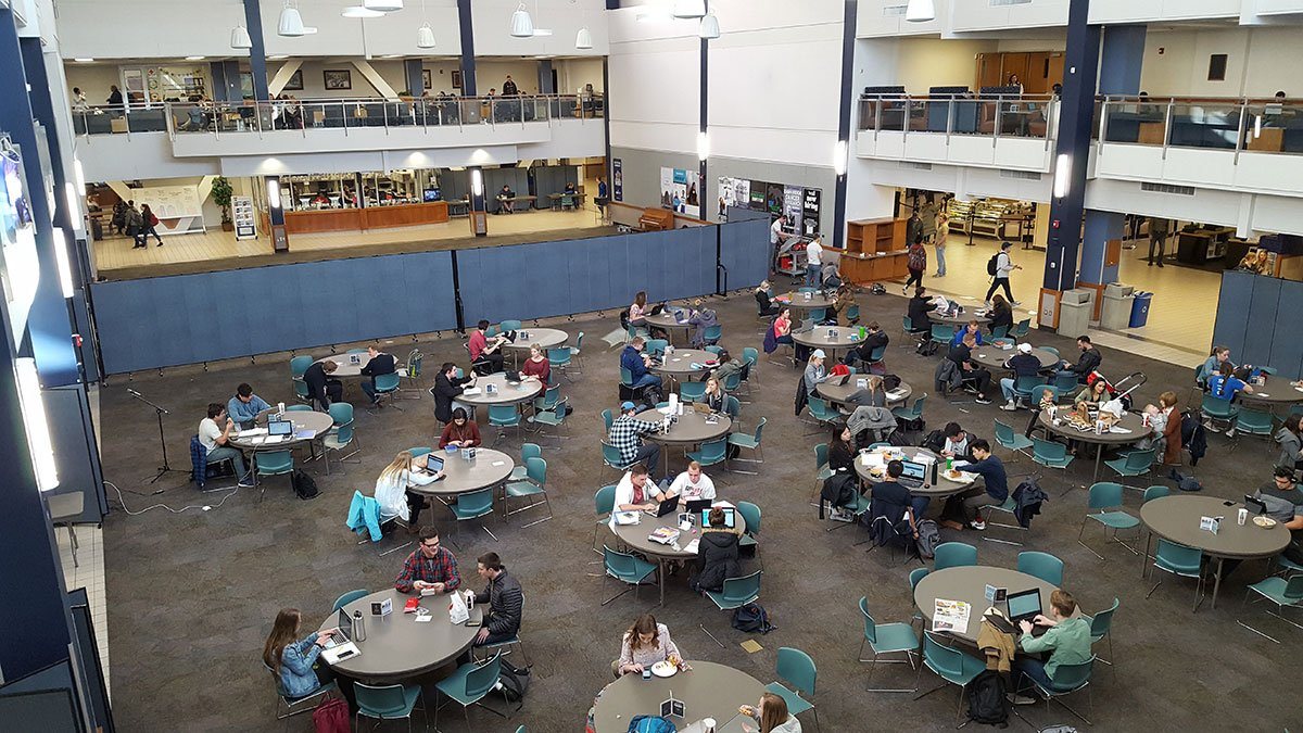Students sit at round tables in a large room while a set of blue room dividers restrict access to other side