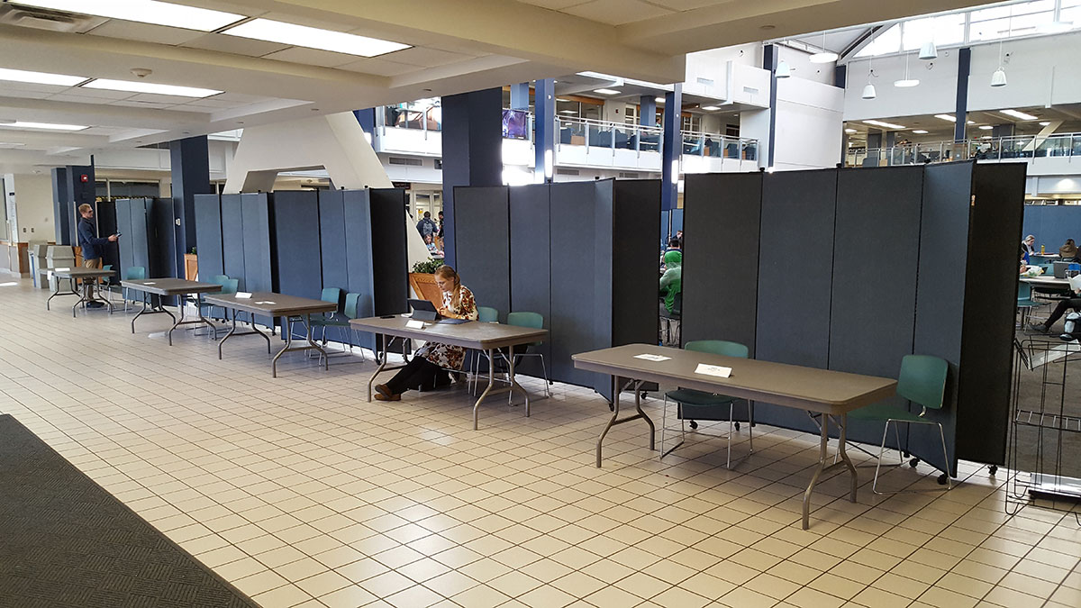 A female student sits at a long table in a hallway with blue display towers behind her