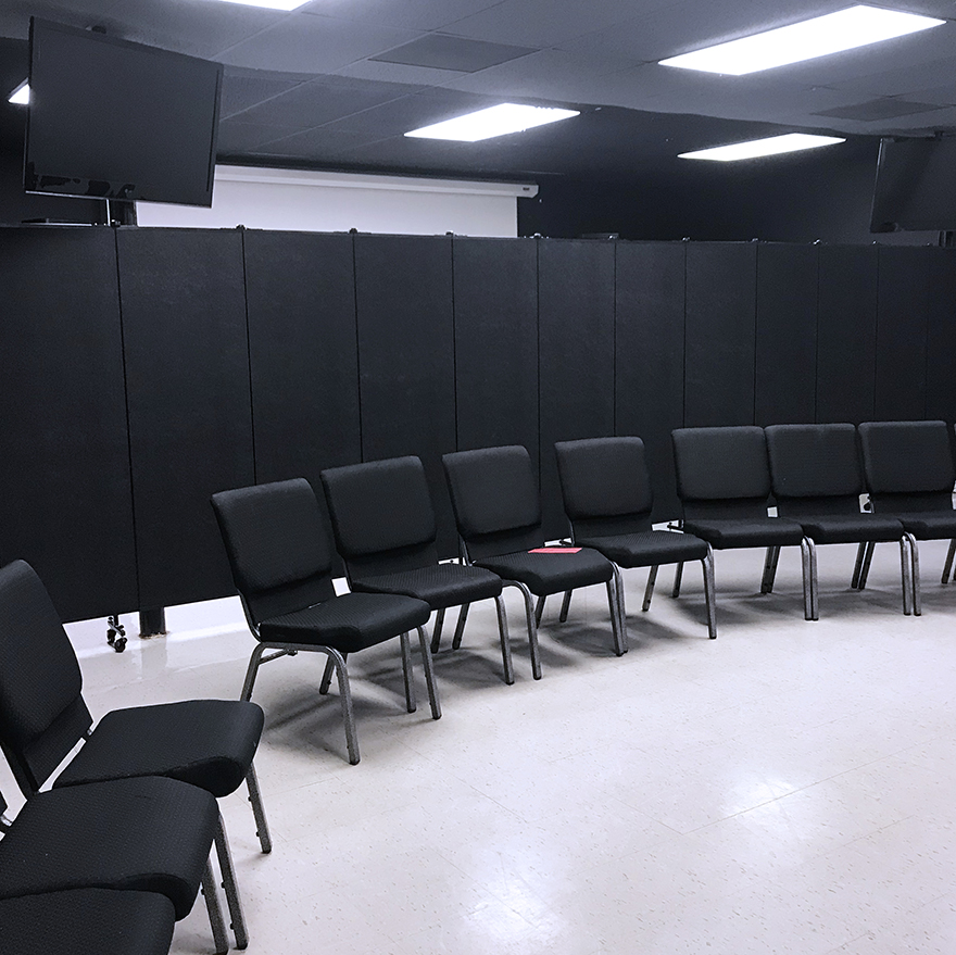Black portable partition divider opened in a classroom with a set of chairs set in a row in front of it.