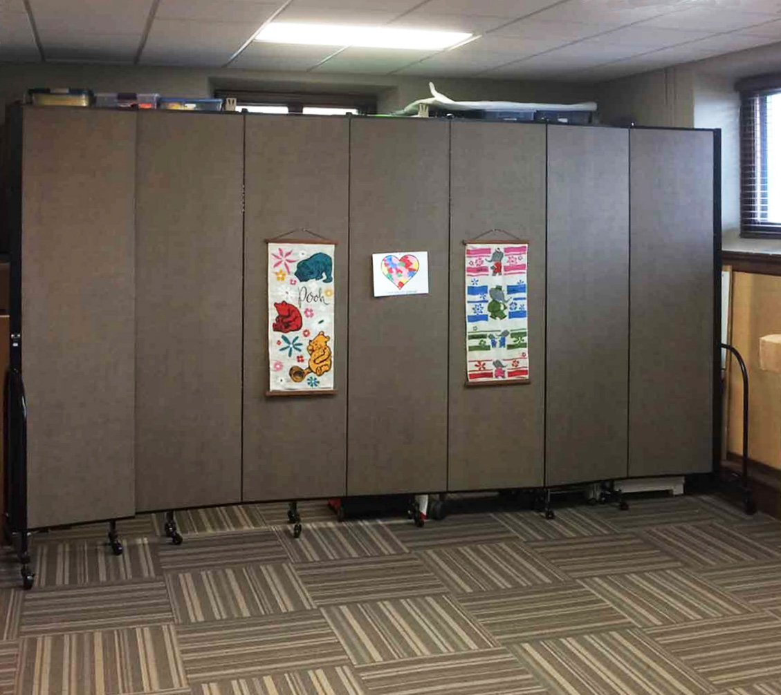 Posters are tacked to a 7-panel Screenflex folding wall partition that is opened in a classroom