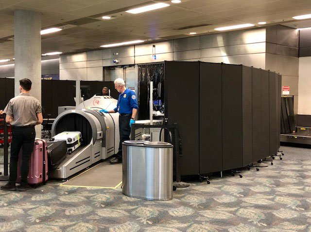 Movable privacy screen around luggage screening